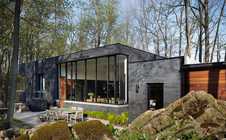 Contemporary home in the forest featuring dark brick exterior 2