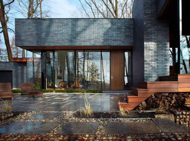 Contemporary home in the forest featuring dark brick exterior 3