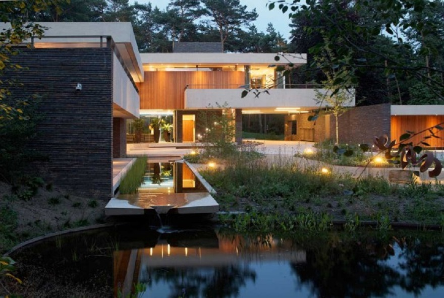 Home exterior with large swaths of natural wood which softly lit at night 2
