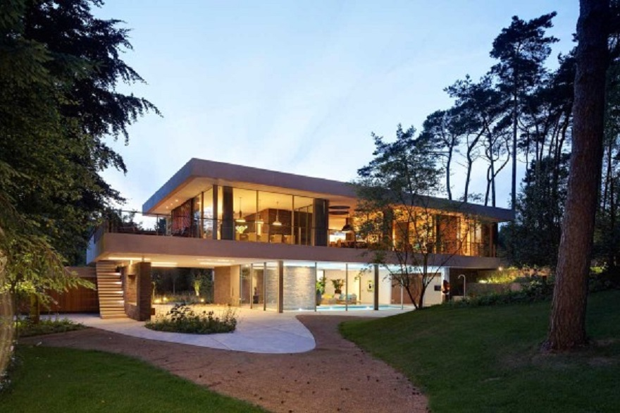 Home exterior with large swaths of natural wood which softly lit at night 5