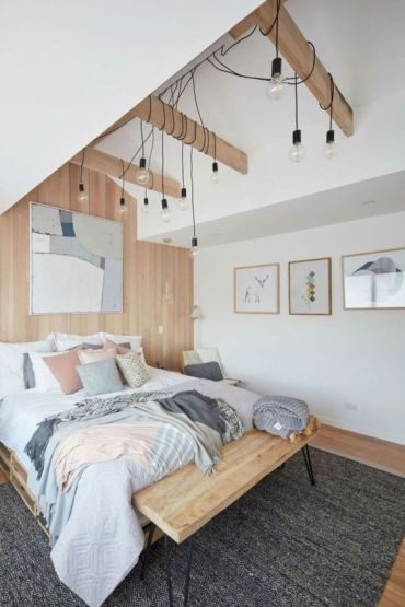 A-scandinavian-bedroom-with-a-wooden-bed-and-bench-some-bulbs-hanging-down-and-pastel-touches