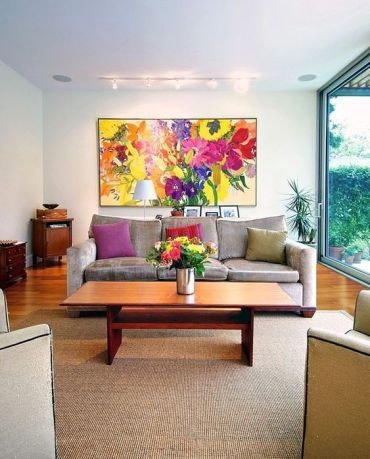 A-bold-floral-artwork-bold-blooms-in-a-vase-and-colorful-pillows-to-make-your-living-room-extra-bold