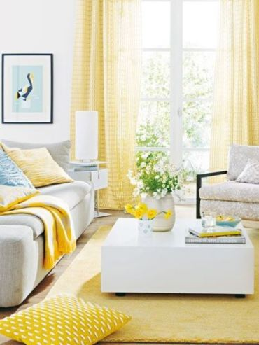 A-vivacious-living-room-with-yellow-curtains-a-rug-and-some-pillows-feels-sun-filled-and-very-bright