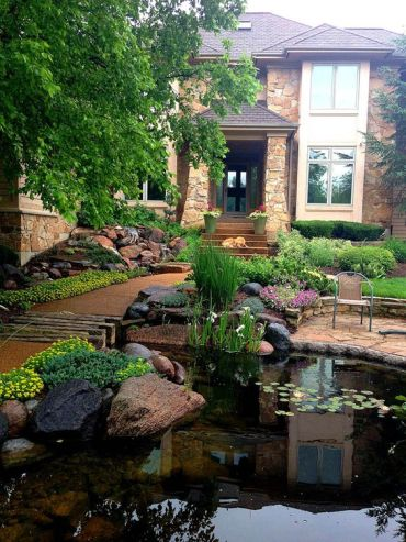 10-a-large-pond-decorated-with-rocks-with-blooms-and-greenery-makes-this-front-yard-stunning