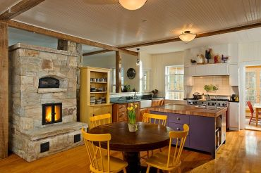Farmhouse-style-kitchen-of-new-york-home-with-colorful-decor-and-a-lovely-stone-fireplace