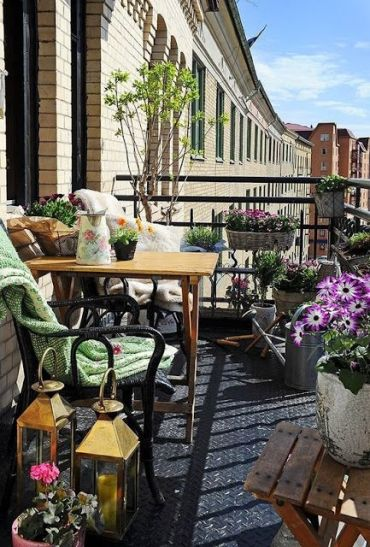 A-refreshing-summer-balcony-with-potted-greenery-and-blooms-rattan-and-wooden-furniture-candle-lanterns-and-textiles