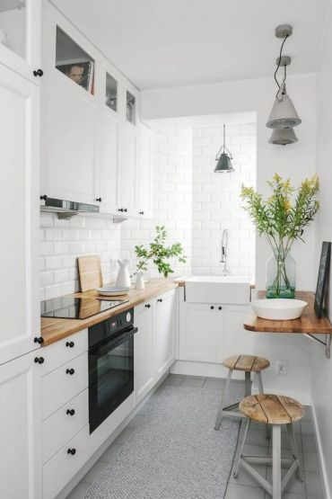 A-small-nordic-kitchen-with-white-cabinets-black-hardware-butcherblock-countertops-and-white-tiles-plus-wood-and-metal-stools