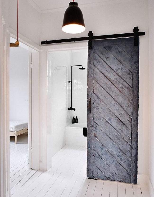 Reused-old-barn-door-creates-a-fabulous-entrance-for-the-scandinavian-bathroom