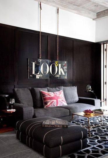 A-contemporary-masculine-living-room-with-dark-walls-upholstered-furniture-a-printed-rug-a-metal-table-and-a-sign