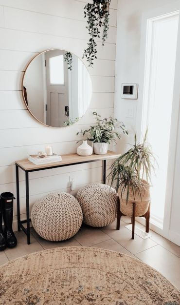 A-neutral-modern-entryway-with-a-wooden-console-crochet-ottomans-potted-plants-and-a-round-mirror-is-chic
