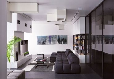 White-grey-black-living-room-indoor-plants-glass-end-tables-celing-lamps-glass-shelves-tv-tinted-glass-doors-ottoman-abstract-wall-art