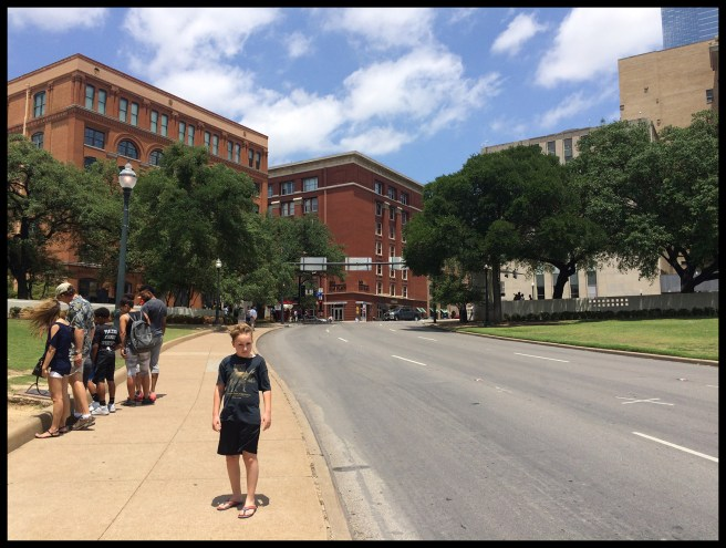 """The building on the left is where Oswald hid and waited to the President's motorcade. The """"x"""" on the street on the right was where the first shot hit."""
