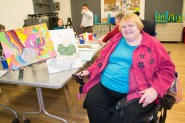 Virginia Ellen Cutmore, 60, joined the Laser Eagles as an artist two years ago. She poses in front of her paintings she drew over the past year.