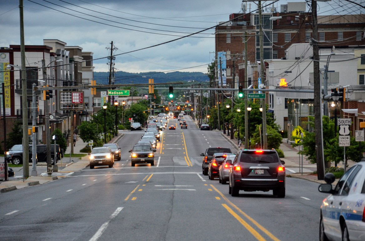 A photo, taken from the center lane of the Baltimore Avenue-slash-Route 1 corridor looking directly south from the intersection of Oglethorpe Street and Baltimore Avenue, shows an urban vista. The green hills of Bladensburg are in the far distance, set against a cloudy evening sky and above a ribbon of roadway. Nearer to the photographer, an urban streetscape reveals row-houses and mid-rise commercial buildings south of Madison Street set against tree-lined sidewalks. Light traffic is seen on the roadway.