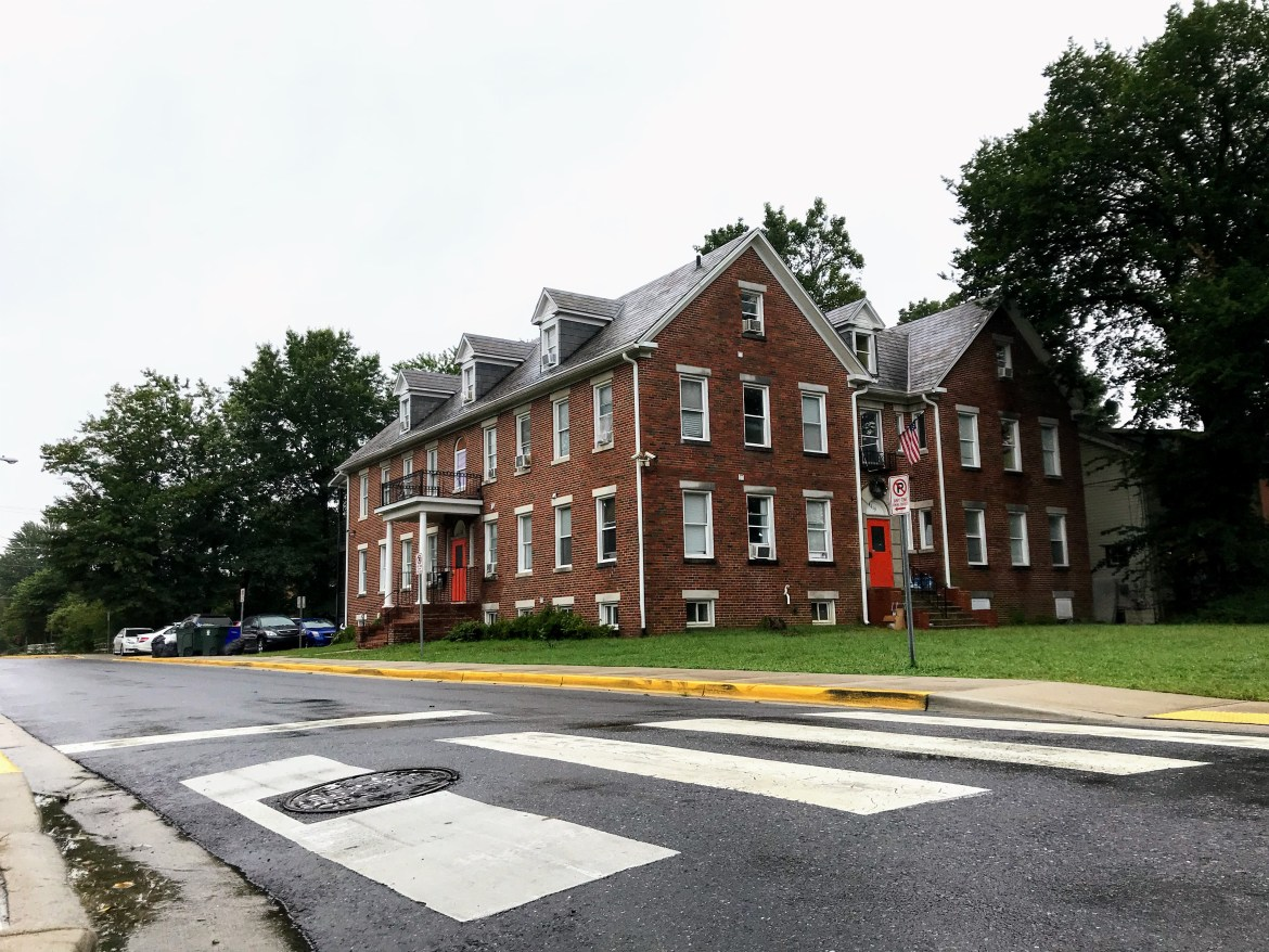 A medium-sized two-story brick apartment building sits on a large yard infront of a wet two-lane residential roadway. The sky is grey, trees in the background are leafy and green.