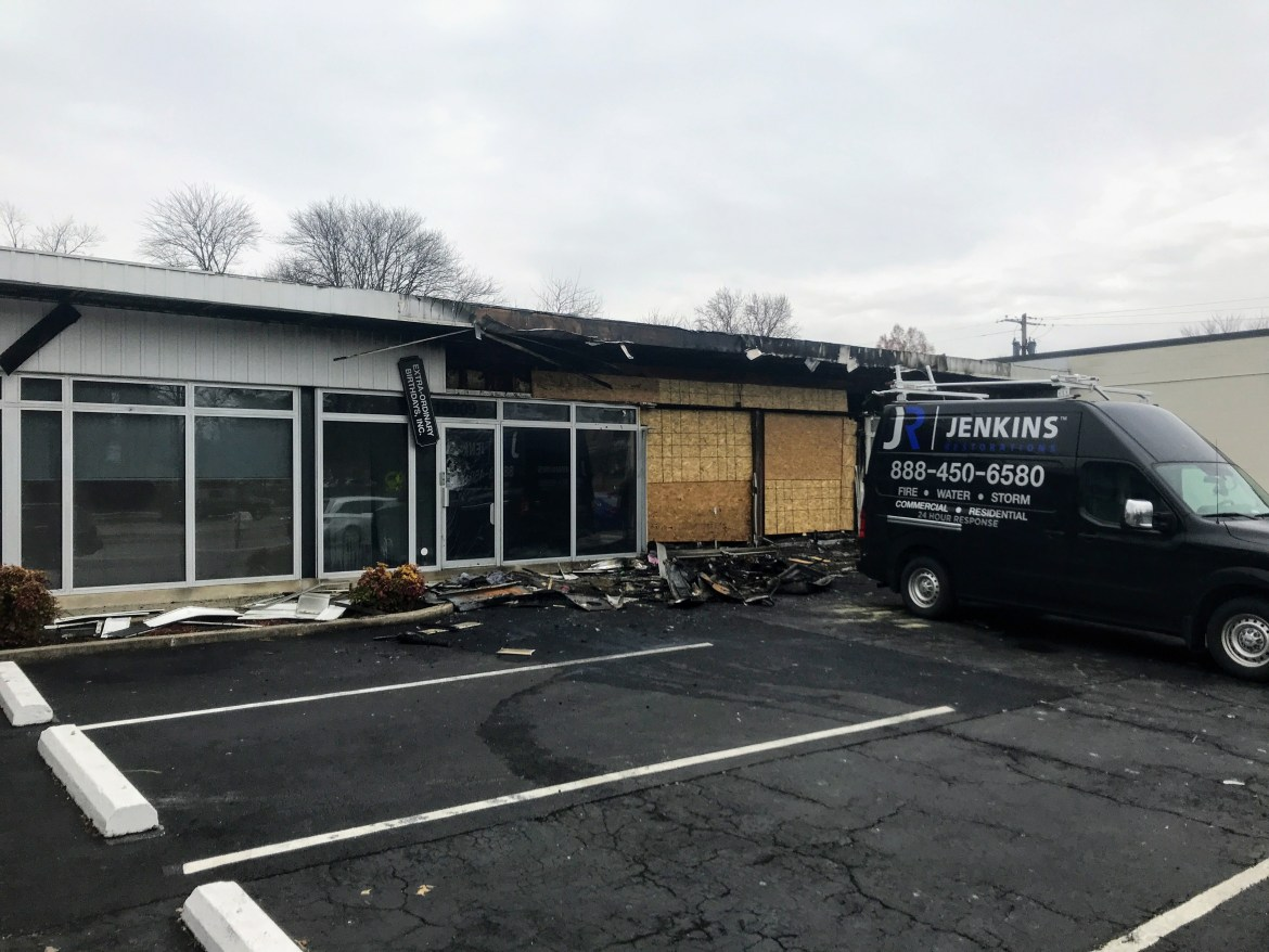 """A small suburban storefront is seen, it has clearly suffered a large fire. Charred debris litters the parking lot. The burned storefronts are boarded up with plywood, a van from a """"Jenkins Restoration"""" company is parked outside, bearing the business phone number."""