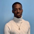 A thin-built African-American man stands against a blue background, looking into the camera. This is DeMornai Blackwell. He is wearing a white cable-knit turtle neck sweater and a gold pendant on a thin chain around his neck.