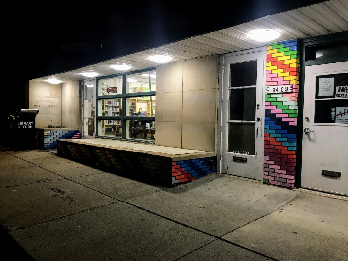 A small storefront is seen at night, it features a column of rainbow-colored bricks. The inside is brightly lit, seen through large windows next to a far door.