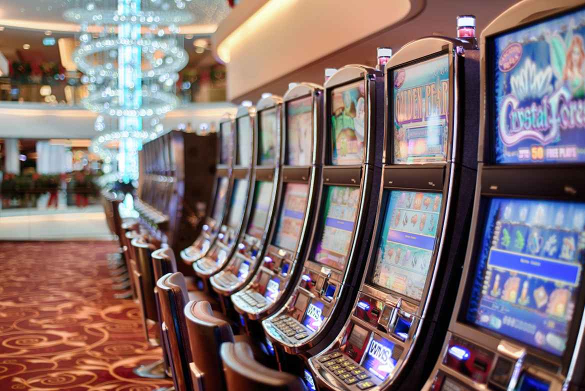 A line of slot machines recedes into the distance at a casino.