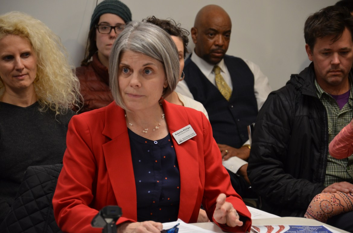 Centered in the image, a white woman with grey hair, wearing a red blazer and dark blouse, looks across a conference table at a crowded meeting in a small white room.