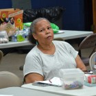 A middle-aged African-American woman with gray hair and a white, short-sleeved shirt sits at a table during a meeting of some kind.