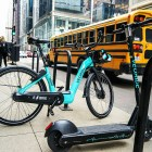 A VeoRide e-bike and scooter are seen parked near bicycle racks on a busy street in a company stock image.