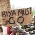 a photograph of protesters in cameroon holding up a sign that says 'biya must go' on it in black lettering