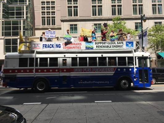 A bus full of protestors makes its way down Market Street.