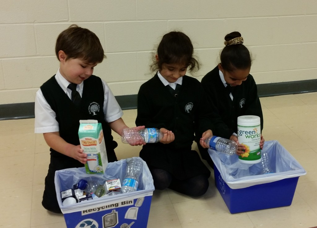 Grade 1 students setting aside plastic bottles and paper materials to be used for our upcoming Science Fair