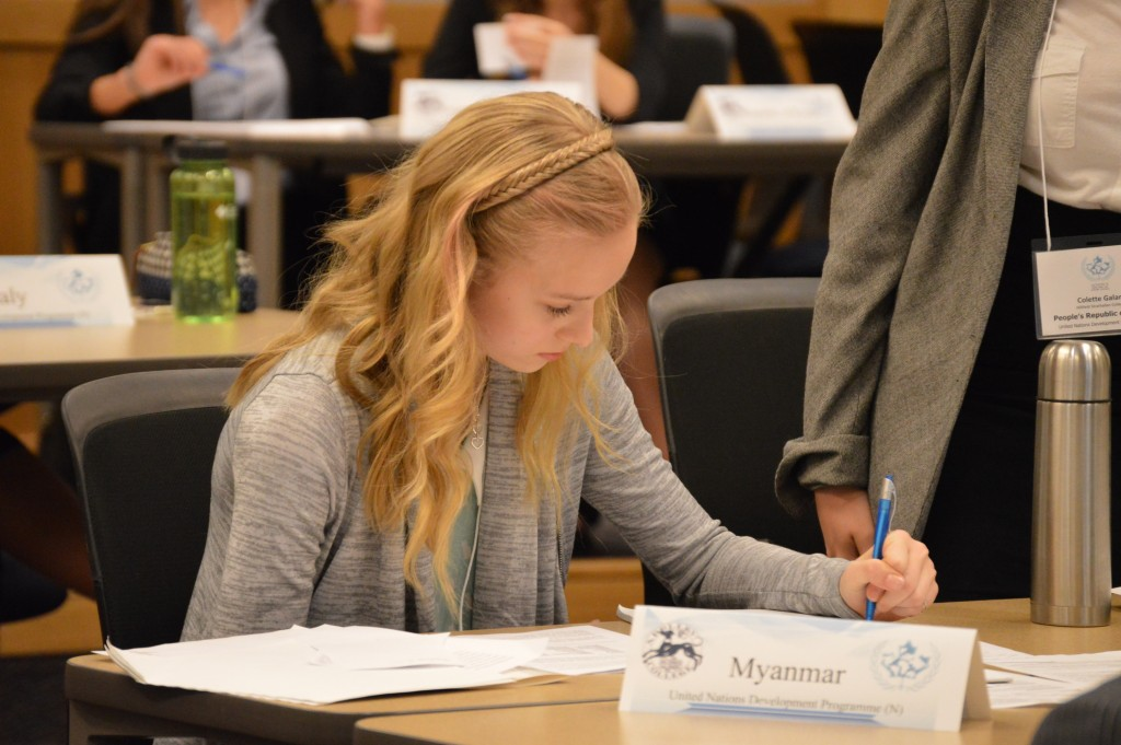 A RMS student delegate strategizing during a committee session