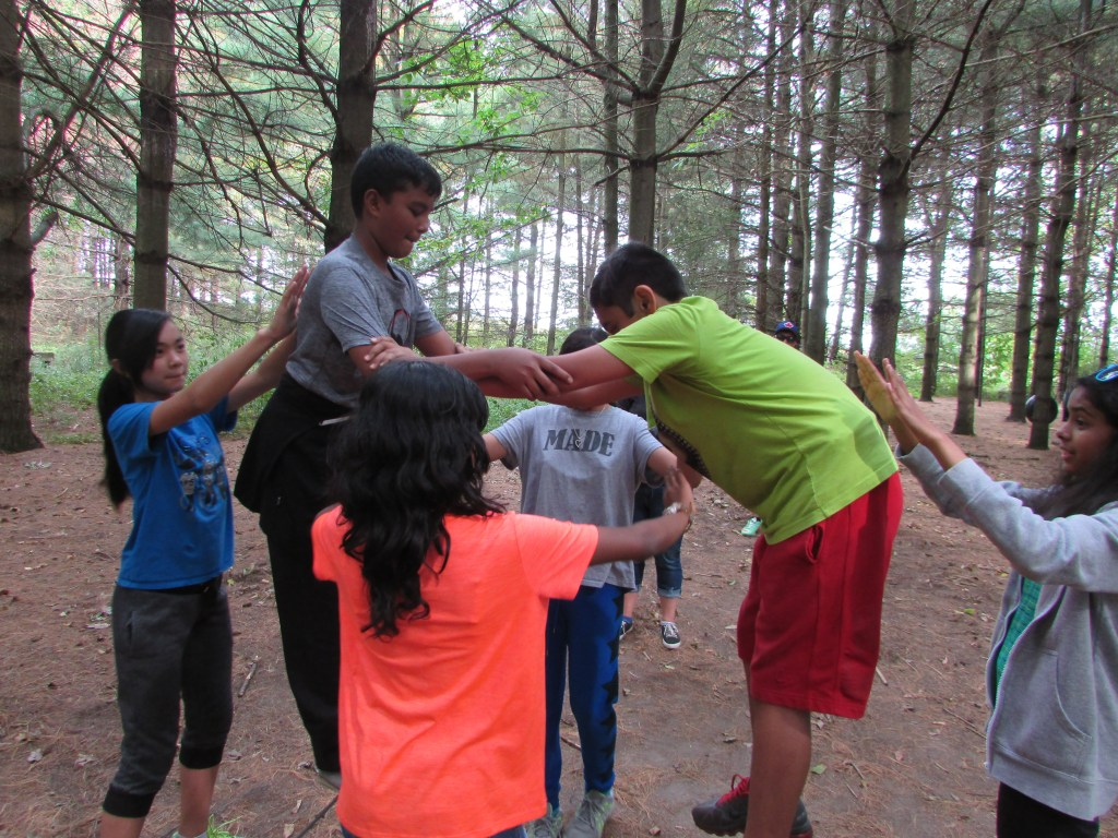 Students at leadership camp demonstrating their teamwork skills on the low ropes