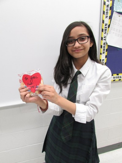 RMS student holding Valentine's Day donation for chairty