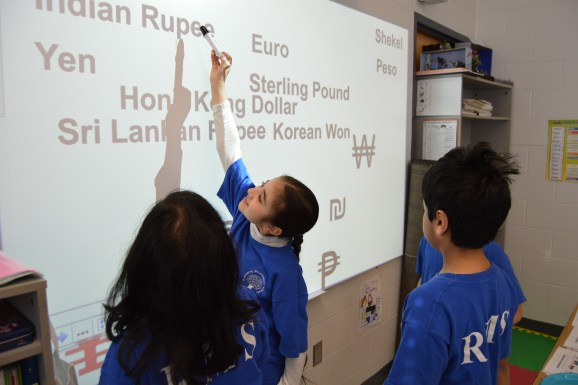 Students doing a math activity on the interactive whiteboard