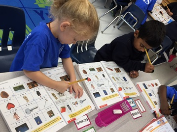 Kindergarten students learning to read by using worksheets at private school in Brampton