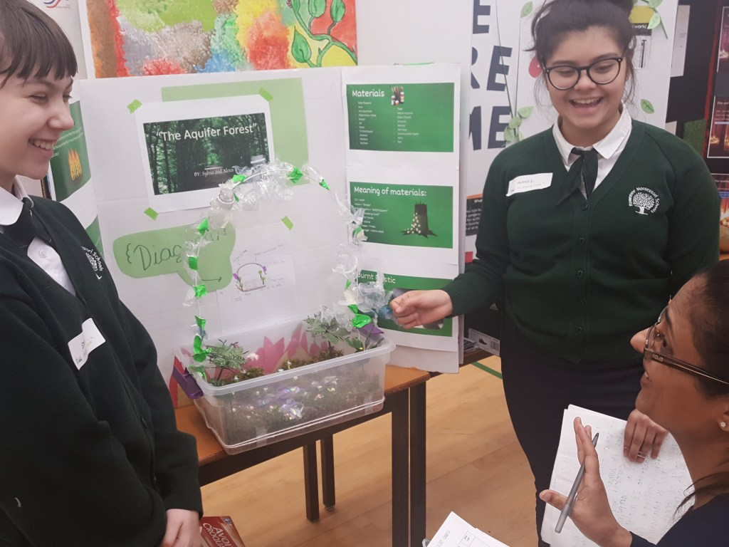 Students showcasing their prototype of an aquifer forest dome that will work to keep forest floors moist and reduce forest fires.