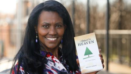"Shegitu Kebede holds her newest book ""Appeal to Heaven"" on Nov. 11, 2016, in downtown Fargo. Michael Vosburg / Forum Photo Editor"