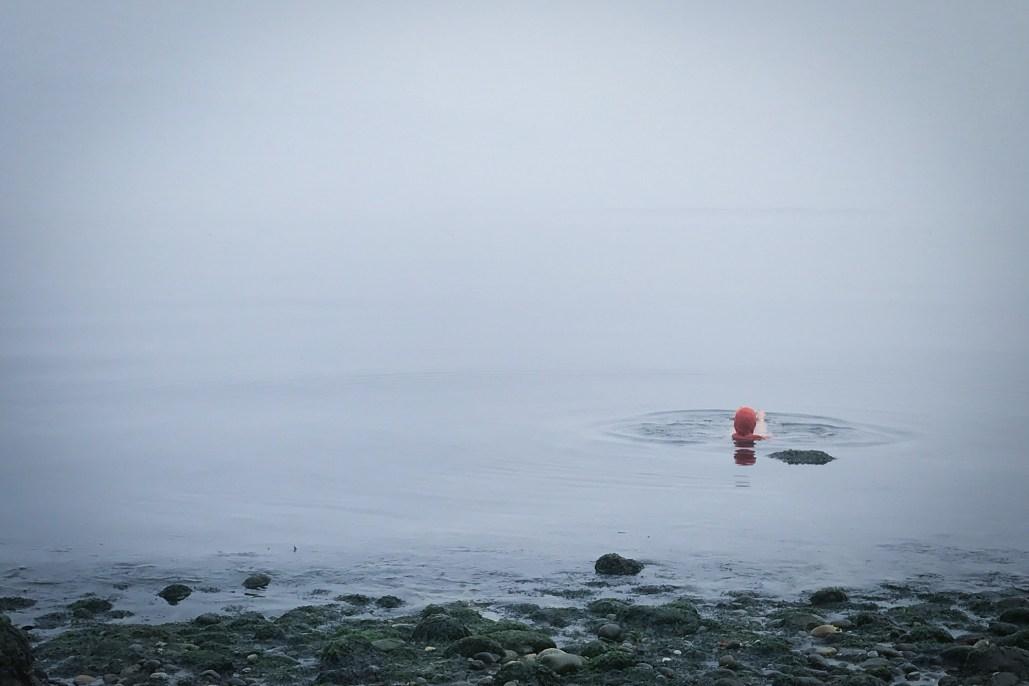 photo of woman in a still blue sea