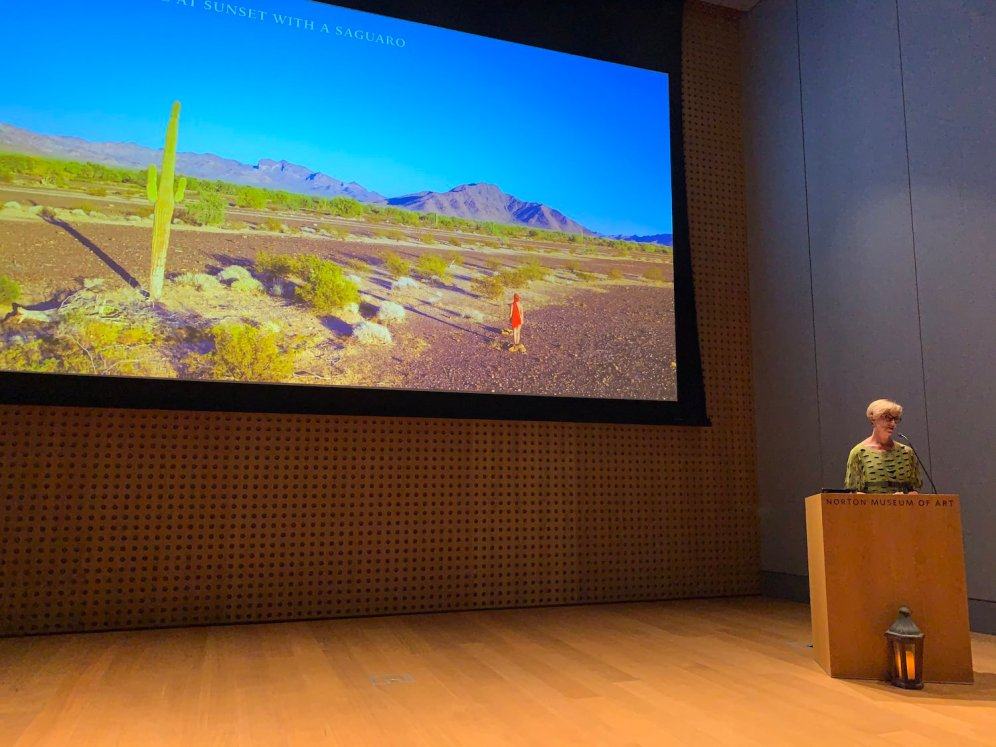 Roxanne Darling at the podium at the Norton museum of art speaking on climate change
