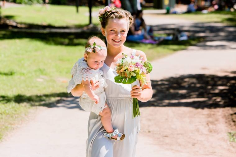 Nicole Laufer Photography.  Baby being carried down the aisle by her sister at Shorncliffe, Brisbane.  Celebrant Roxy Hotten