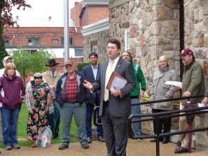 On May 4, Daniel Pond III explained the Real Estate Auction process as interested buy-ers, then-Assistant County Attorney Dan Whitten (background, cool black hat and shades), among others, listen.
