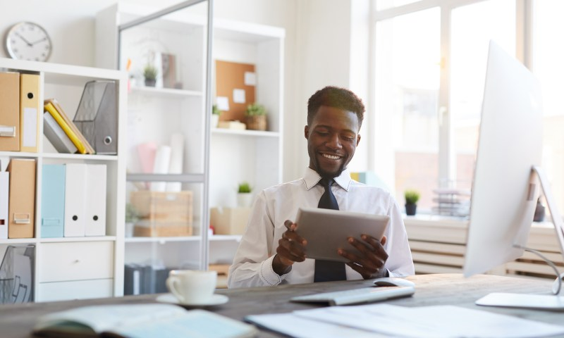 Young smiling African-american businessman with tablet