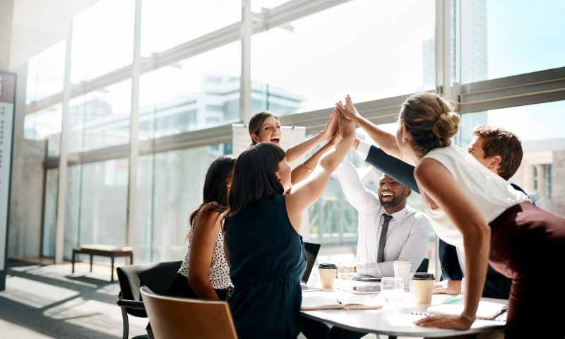 A group of businesspeople high fiving, symbolizing the beginning of a real estate career.