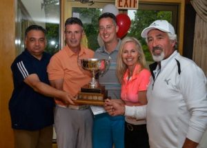 Gus Monteleone (far left) presents the winning foursome at the 23rd Annual GTA Charity Golf Tournament with their trophy, from L to R:  Michael Stothers, Alun Evans, Caroline Baile and Mario Hermenegildo.