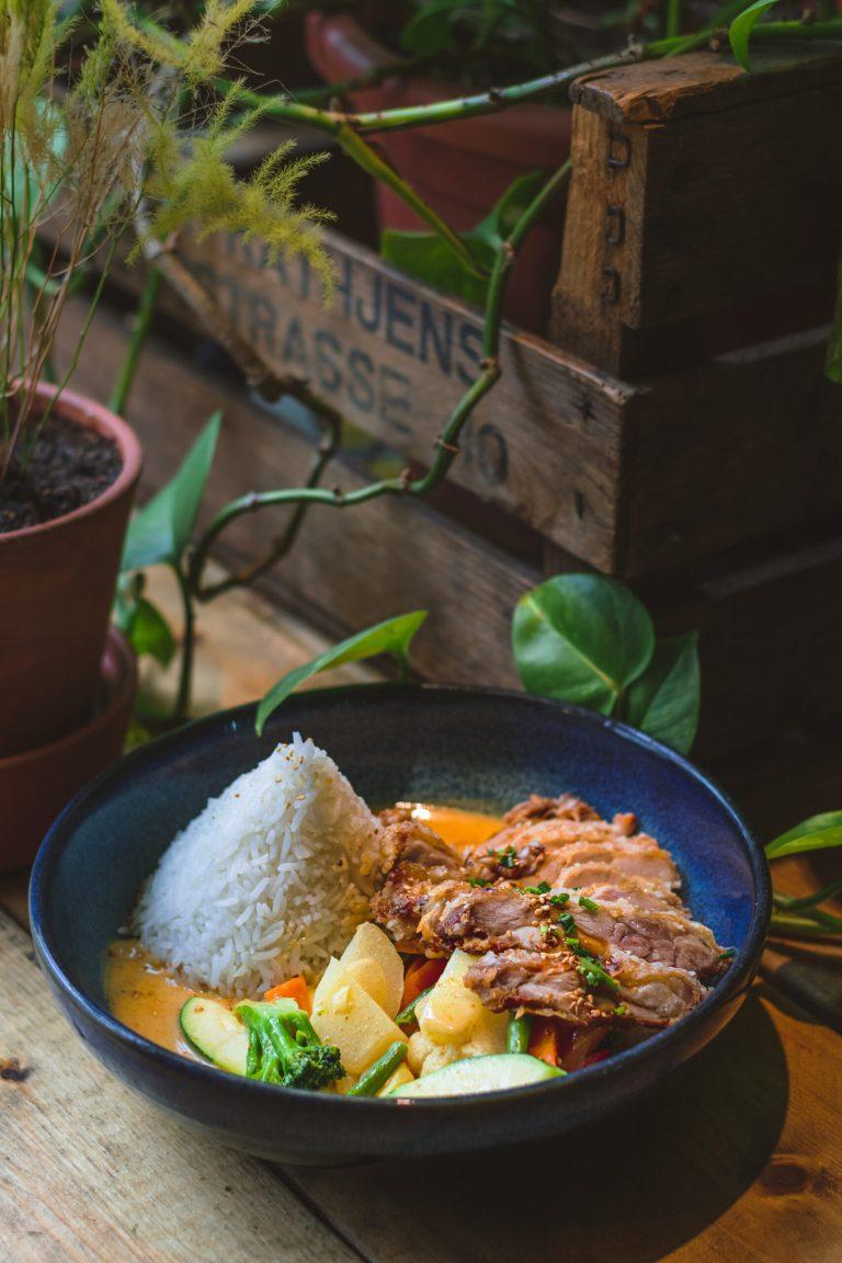 Leckeres gebackenes Hähnchencurry serviert mit Reis im Restaurant Royals and Rice