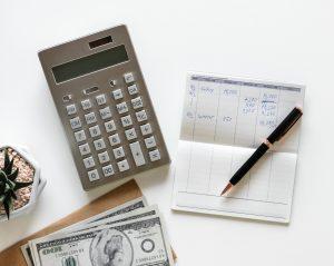 ołówek z kartk, kalkulatorem oraz pieniędzmi