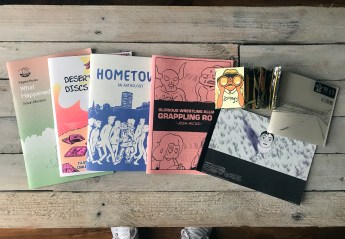 The haul! L-R: What Happened by Simon Moreton, Desert Island Discs Fanzine edited by Sammy Borras, Laydeez do Comics Hometown Anthology, Glorious Wrestling Alliance: Grappling Road by Josh Hicks, Zoology by Jo Berry, The Fields Beyond Episode 1 by Matthew Pettit and M69 by Nick Soucek