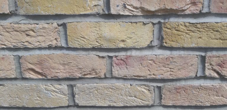 Accent yellow brick cladding close up scaled - Cladding and Finishes