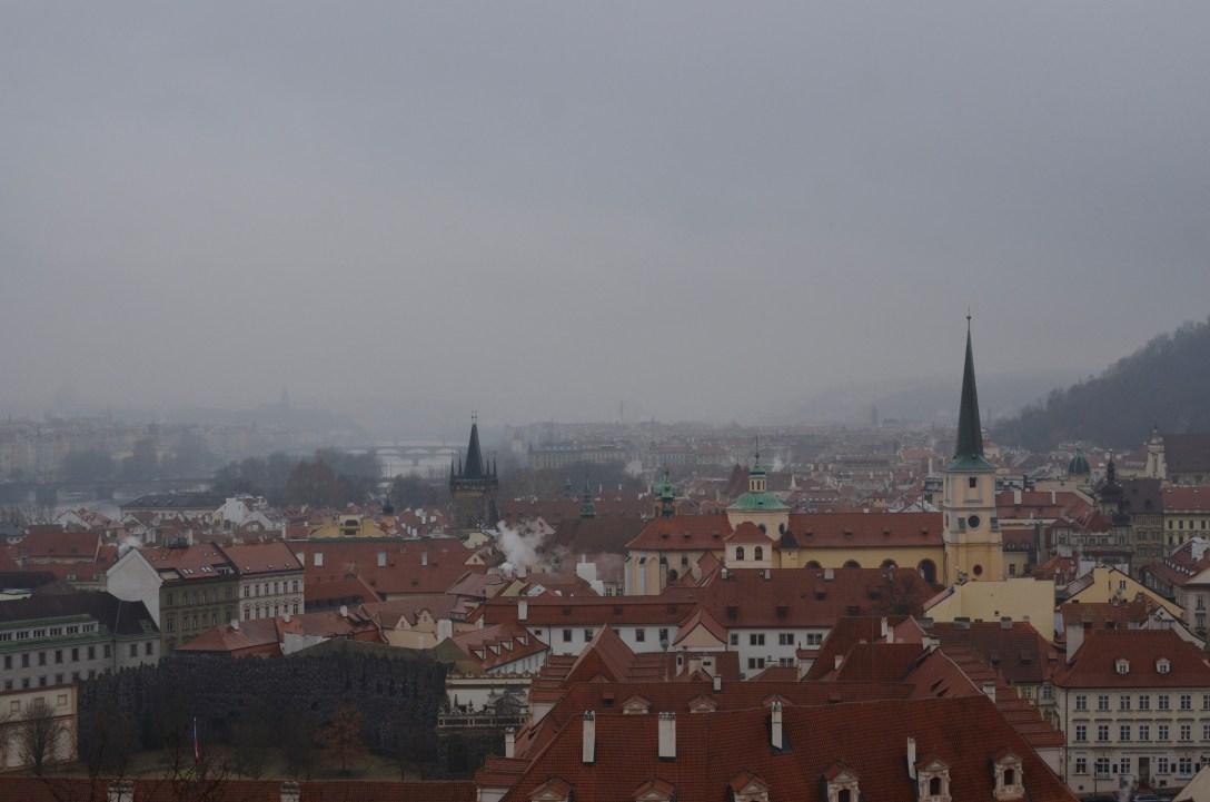 Photo de Prague. On y voit des toits, un fleuve, un pont, de la brume et des fumées de cheminées.