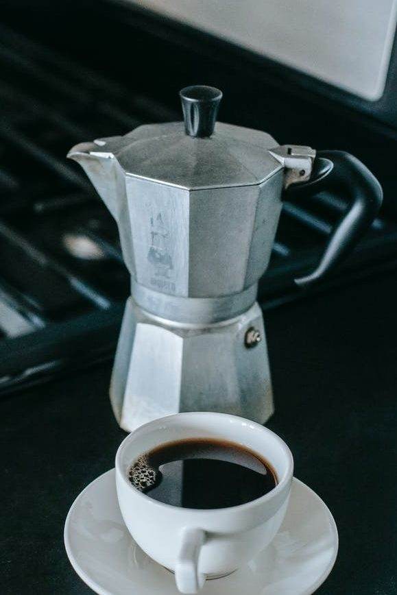geyser pot with cup of coffee placed on table in kitchen