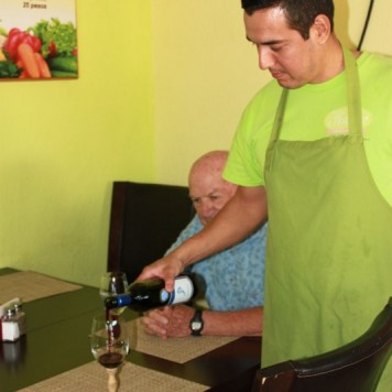 [Alfonso serving wine] Velazquez takes a moment from the grill to greet and serve customers.